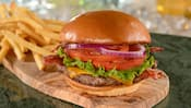 A hamburger on a bun with cheese, lettuce, onions and tomatoes, served on a wooden plank with French fries