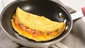 Dans une poêle se trouve une grande omelette western, remplie de jambon coupé en dés, de légumes et de fromage