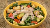 A salad containing kale, pickled onions, avocado, tomatoes, shredded chicken and dressing
