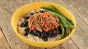 A bowl of braised beef stew, black beans and stringed beans over rice