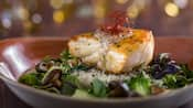 A piece of black grouper on a bed of rice surrounded by vegetables