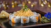 Sushi placed in a circle on a wide plate with a flower on the side