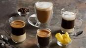 Uma variedade de 4 bebidas de café em copos de diversos tamanhos