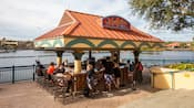 Guests lounging around a walk-up bar located near a body of water