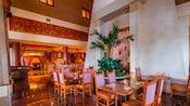 O salão de jantar de um restaurante com pé-direito alto, plantas e decoração mexicana contemporânea