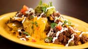 A plate of nachos topped with cheese sauce, ground meat, guacamole, cilantro and sour cream