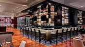 A modern bar featuring liquor in glass cases and over a dozen elegant stools