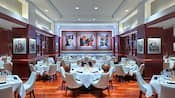 A dining room with formally set tables and photos of the Miami Dolphins on the walls