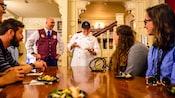 Um Guia VIP Tour assiste a um chef servindo um prato de degustação para os Visitantes em uma mesa de jantar