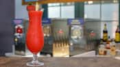 A frozen, blended cocktail in a Hurricane glass garnished with a strawberry and pineapple wedge sits on a counter in front of frozen drink machines and liquor bottles