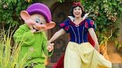Perto da porta de uma humilde choupana e um gramado, uma sorridente Snow White caminha de mãos dadas com Dopey, um dos 7anões