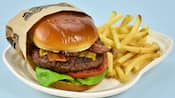 A cheeseburger with lettuce, tomato and bacon served with french fries