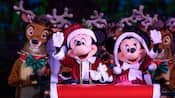 Mickey and Minnie, dressed like Santa and Mrs. Clause, ride down a sleigh surrounded by reindeer