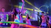 A Guest hula hoops to music in a nightclub like setting while others look on