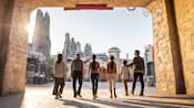 A family walks through a tunnel into Star Wars Galaxy's Edge, a land with tall petrified wood spires and Star Wars style buildings