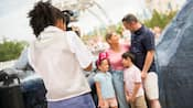 A Disney PhotoPass photographer taking a picture of a happy family near Tomorrowland