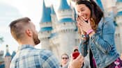 A man proposes to a woman in front of Cinderella Castle