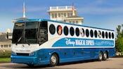 Com imagens do Mickey, Minnie, Donald e Daisy, o ônibus do Disney's Magical Express situa-se em frente a diversos edifícios do Walt Disney World Resort