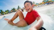 With a sea of umbrellas dotting the beach, a happy young boy in an inner tube floats around the water