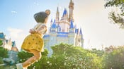A young girl jumping while surrounded by bubbles near Cinderella Castle at Magic Kingdom park