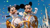Mickey Mouse and Minnie Mouse standing atop a parade float near Cinderella Castle
