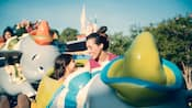 A mother and her daughter riding the Dumbo the Flying Elephant attraction at Magic Kingdom park
