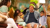 Family with 2 young children playfully tugging on the father's Goofy hat