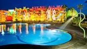 Una piscina al aire libre y el exterior del Disney's Pop Century Resort iluminado por la noche