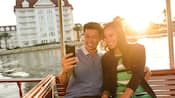 A man and woman taking a selfie while riding in a boat