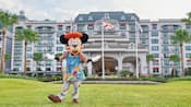 Mickey Mouse dressed as an artist on the vast lawn in front of Disney's Riviera Resort.