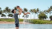 A father stands in a lagoon near a beach with palm trees, holding his toddler son up in the air