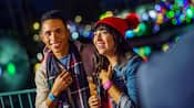 A man and woman in warm clothing smiling at holiday lights