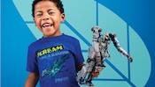 """Un niño pequeño sosteniendo un juguete de traje mecánico de Avatar, con una camiseta con un banshee y el texto """"scream like a banshee, Pandora"""""""