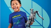 """A little boy holds an Avatar mechanical utility suit toy and wears a t shirt with a banshee and the words """"scream like a banshee, Pandora"""""""
