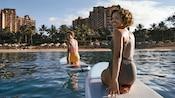 Duas mulheres de joelhos em pranchas de stand-up paddle no mar em frente ao Disney Aulani Resort