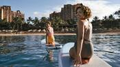 Two women kneeling on paddle boards in the ocean off of Disney Aulani Resort