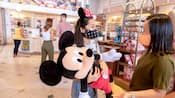 A young girl holding an oversized Mickey plush inside the Emporium at Magic Kingdom park