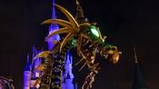 Maleficent passando pelo Cinderella Castle em forma de dragão à noite