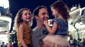 Un hombre sostiene a 2 niñas sonrientes