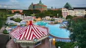 The pool area of Disney's BoardWalk Inn featuring 2 multistory buildings, leafy trees, a carousel shaped snack bar and a waterslide fashioned to look like a roller coaster