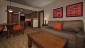 Le salon d'une villa avec un mélange de meubles en bois et de meubles rembourrés, et une cuisine