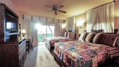 An African themed bedroom with 2 Queen beds, animal print carpeting, desk with chair, ornate entertainment center with dresser drawers, ceiling fan and sliding glass doors leading to an outdoor patio