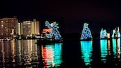 A sea monster made of lights on a lake near a hotel