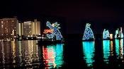 Un monstruo marino hecho con luces, en un lago, cerca de un hotel