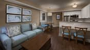 A guest room with a sofa, coffee table, wall art, a dining area and an open kitchen with counter seating