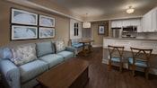 Um quarto com um sofá, mesa de centro, quadro na parede, uma área de jantar e uma cozinha aberta com balcão com assentos