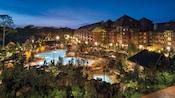 Árboles alpinos rodeando un hospedaje de varios pisos en madera y piedra con una impresionante área de piscina