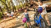 Dos niños caminando con sus bicicletas en la mano junto a una casa rodante estacionada mientras sus padres observan sentados en sillas plegables