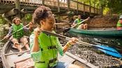 Une femme et sa fille rament dans leur canoë près d'un pont