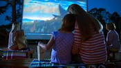 A mother and daughter snuggle while sitting outside watching The Lion King projected on a screen